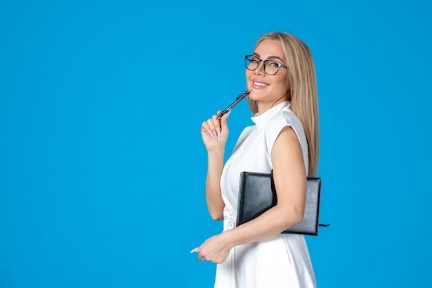 Kobieta z widokiem z przodu w białej sukni pozuje z notatnikiem na niebieskim organie pracy