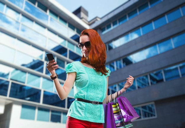 Kobieta z wieloma torbami na zakupy korzystająca z telefonu w pobliżu nowoczesnego centrum handlowego