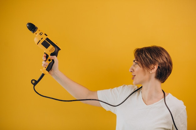 Kobieta z wiertarką elektryczną na żółtym tle