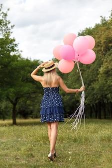 Kobieta z wiklinowym koszu, kapeluszem, różowymi balonami i kwiatami chodzi na wiejskiej drodze
