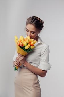 Kobieta z wiosna kwiatu bukietem. szczęśliwa zdziwiona wzorcowa kobieta wącha kwiaty.