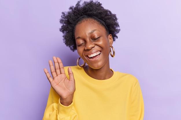 Kobieta z włosami afro trzyma podniesioną dłoń, zamyka oczy, uśmiecha się pozytywnie, pokazuje zęby odizolowane na fioletowo