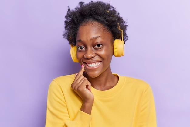 Kobieta z włosami afro uśmiecha się z radością pokazuje białe zęby słucha ścieżki dźwiękowej w bezprzewodowych słuchawkach nosi swobodny sweter na fioletowym tle