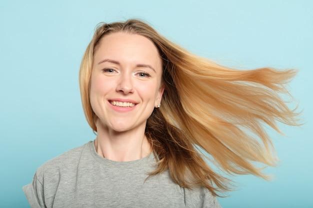 Kobieta z włosami na wietrze. produkty do pielęgnacji włosów i koncepcja piękna.