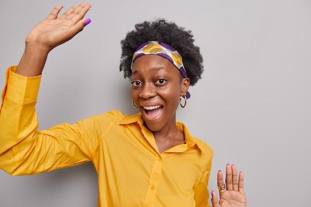 Kobieta z włosami w stylu afro, ubrana w żółtą opaską koszulową, śmieje się radośnie tańczy i bawi się na szarym tle