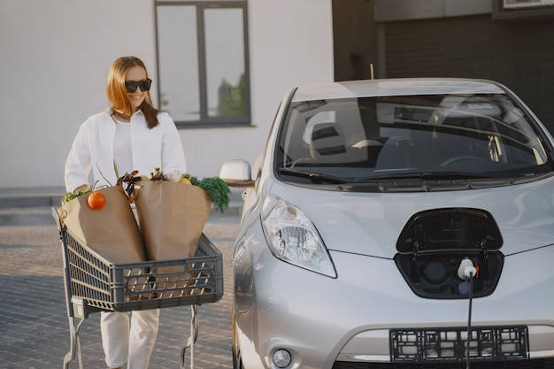 Kobieta z wózek na zakupy jej samochodem