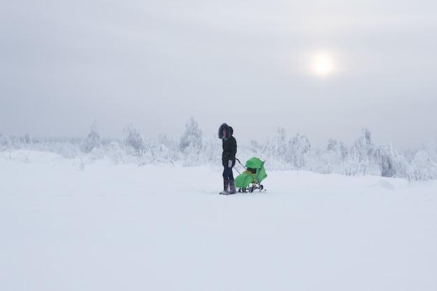 Kobieta z wózkiem dziecięcym spaceruje w zimowym, zaśnieżonym obszarze w mroźny dzień