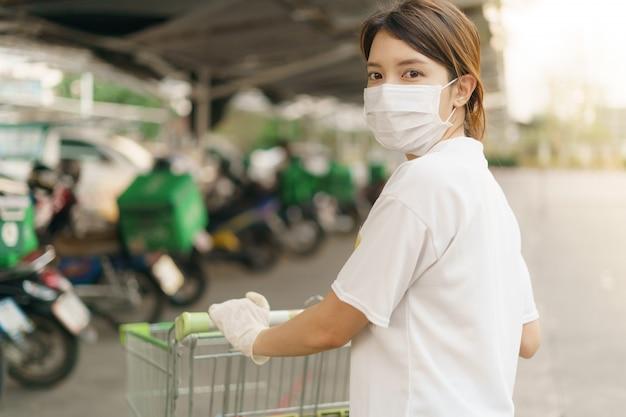 Kobieta z wózkiem na zakupy poza sklepem, ubrana w maskę chirurgiczną podczas pandemii koronawirusa.