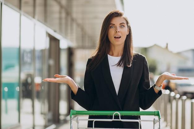 Kobieta z wózkiem na zakupy przy sklepie spożywczym