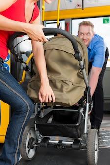 Kobieta z wózkiem wsiada do autobusu