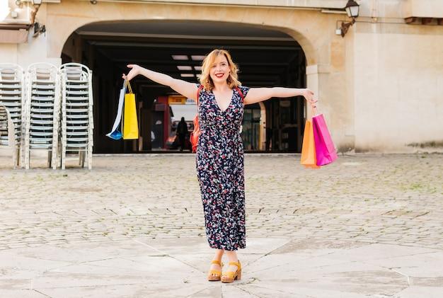 Kobieta z wyciągniętymi na ulicę ramionami i wieloma kolorowymi torebkami w dłoniach, zadowolona z wyprzedaży i rabatów w sklepach.
