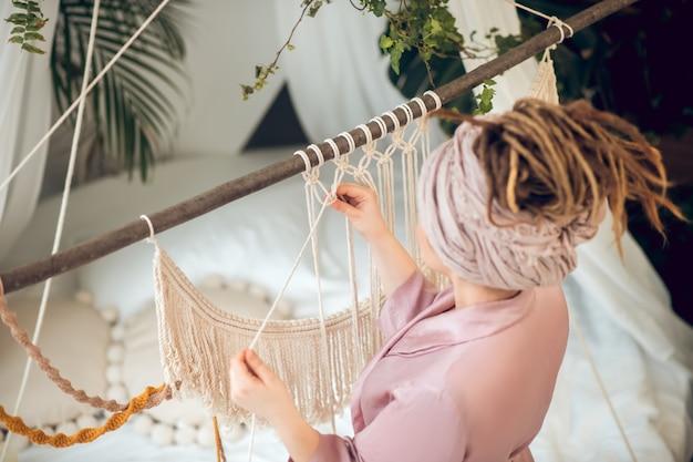 Kobieta z wysoką fryzurą tkającą makramę