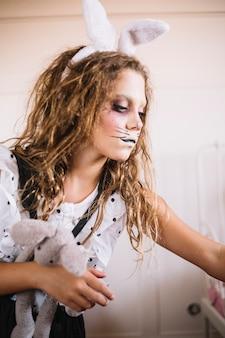 Kobieta z zabawkami w zająca twarzy farby