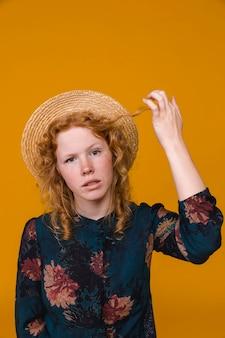 Kobieta z zakłopotaniem dotykając imbirowe włosy w studio