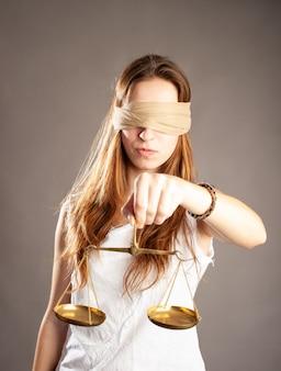 Kobieta z zakrytymi oczami trzymająca skalę sprawiedliwości