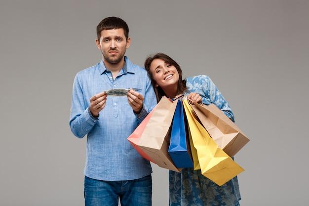Kobieta z zakupami, mężczyzna trzyma ostatnie pieniądze nad szarości ścianą