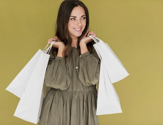 Kobieta z zakupami zarabia netto w obu rękach patrzeje z ukosa