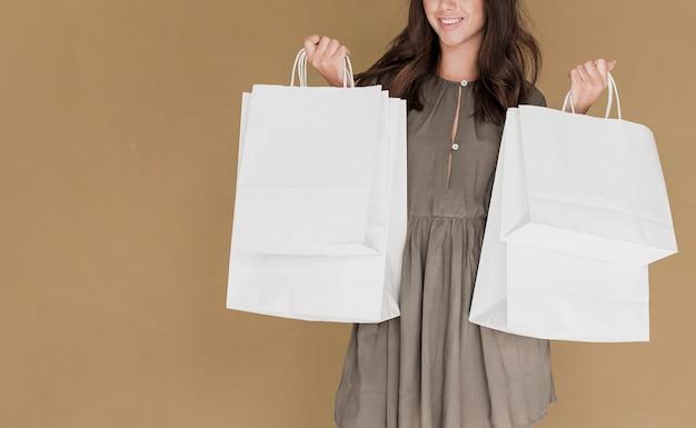 Kobieta z zakupy zarabia netto w oba rękach na brown tle