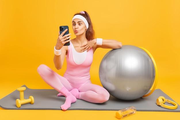 Kobieta z założonymi ustami robi selfie na smartfonie lub prowadzi rozmowę wideo ubraną w sportowe pozy, siada na macie fitness w otoczeniu sprzętu sportowego na żółtej ścianie