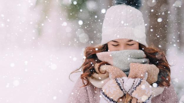 Kobieta z zamkniętymi oczami chowająca się przed śniegiem z szalikiem