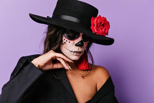 Kobieta z zamkniętymi oczami delikatnie dotyka pomalowanej twarzy. zdjęcie dziewczyny w czarnych ubraniach z czerwonymi detalami.