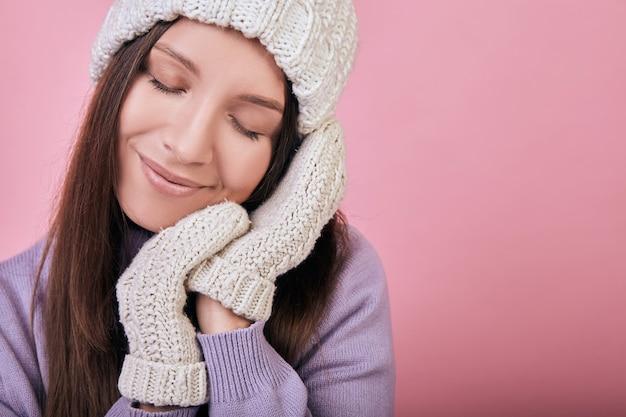 Kobieta z zamkniętymi oczami i splecione dłonie w rękawiczkach pod policzkiem