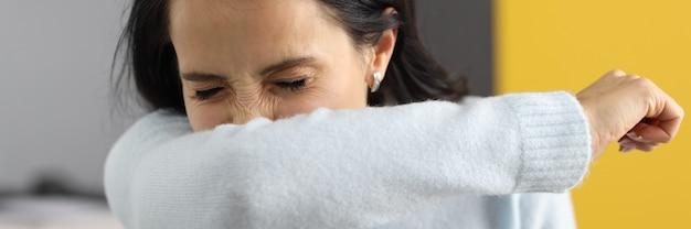 Kobieta z zamkniętymi oczami kichająca w łokieć w domu. profilaktyka infekcji w koncepcji infekcji dróg oddechowych