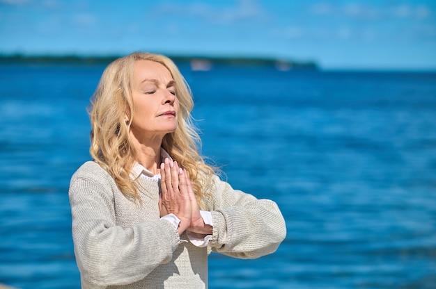 Kobieta z zamkniętymi oczami na tle błękitnego morza