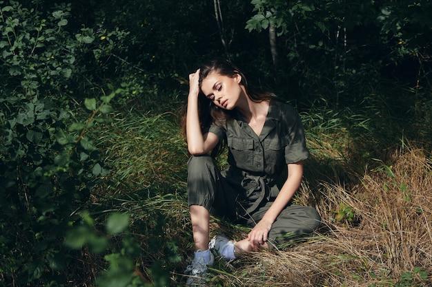 Kobieta z zamkniętymi oczami siedzi na ziemi zielony kombinezon natura lato