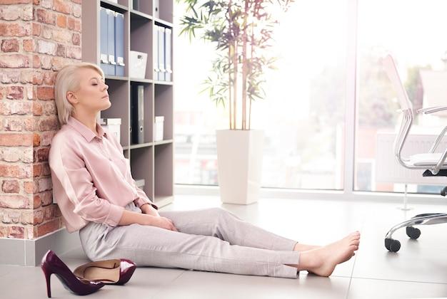 Kobieta z zamkniętymi oczami spoczywa na podłodze