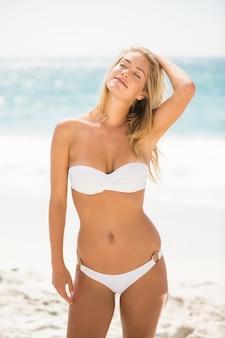 Kobieta z zamkniętymi oczami stojąc na plaży