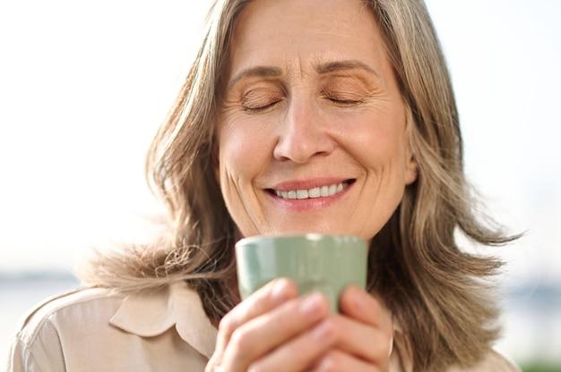 Kobieta z zamkniętymi oczami trzymająca kawę