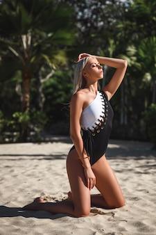 Kobieta z zamkniętymi oczami w stylowy czarno-biały strój kąpielowy siedzi i pozowanie na tropikalnej plaży. niewyraźne tło z palmami. skopiuj miejsce
