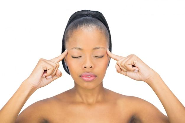 Kobieta z zamkniętymi oczami wskazuje na jej głowie