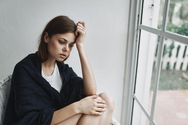 Kobieta z zamyślonym wyrazem w domu w pobliżu wewnętrznego relaksu przy oknie