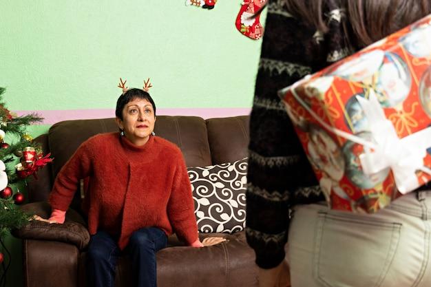 Kobieta z zaskoczeniem czekając na prezent, który ma jej podarować inna kobieta