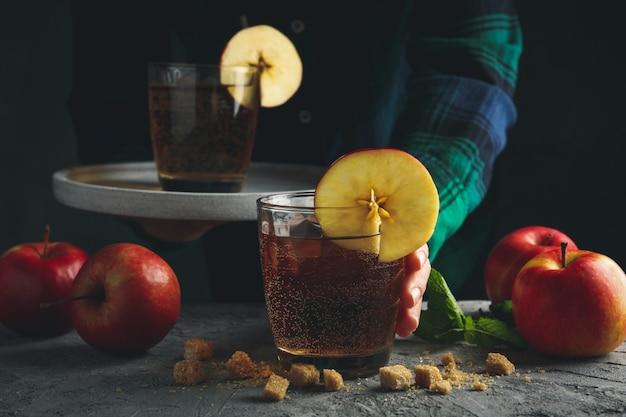 Kobieta z zasobnikiem trzymać szklankę cydru. kompozycja z cydru i jabłka na szarym stole