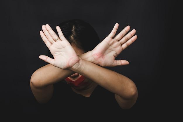 Kobieta z zawiązanymi oczami owijająca usta czerwoną taśmą i pokazująca znak ręką przestaje nadużywać przemocy i nadużyć