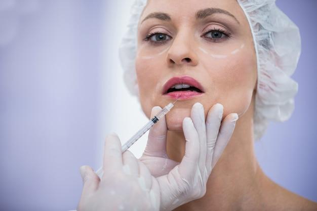 Kobieta z zaznaczoną twarzą otrzymującą zastrzyk botoksu