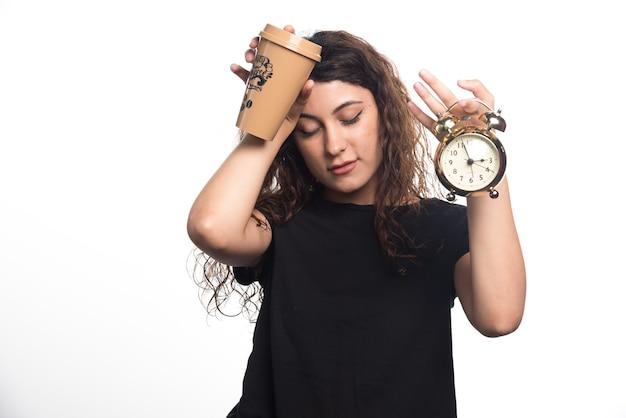 Kobieta z zegarem, trzymając głowę i kubek na białym tle. wysokiej jakości zdjęcie