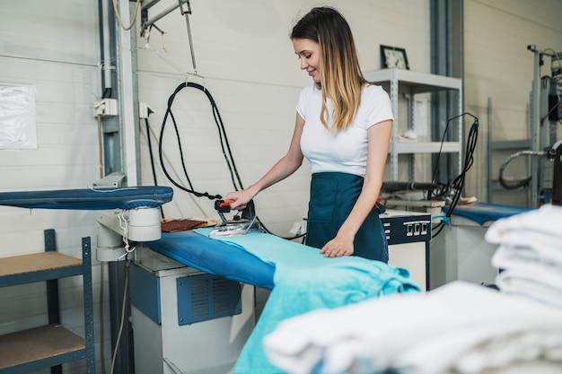 Kobieta z żelazkiem pracuje w sklepie z prasowaniem. usługi sprzątania.