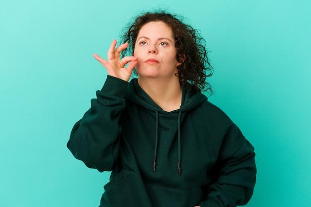 Kobieta z zespołem downa izolowana z palcami na ustach z zachowaniem tajemnicy
