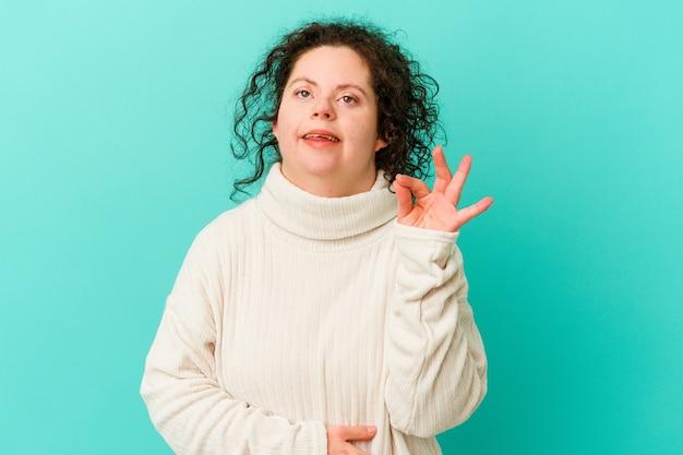 Kobieta z zespołem downa na białym tle mruga okiem i trzyma ręką w porządku gest.