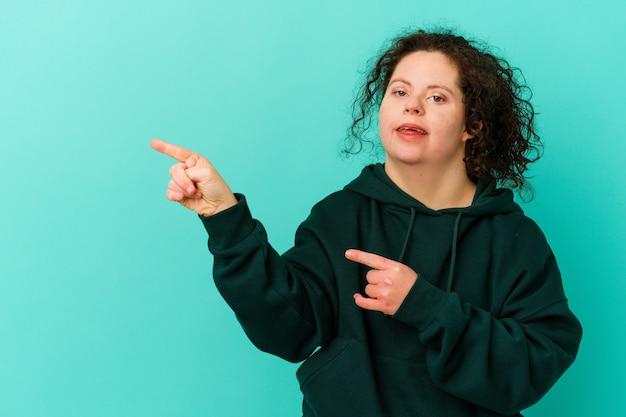 Kobieta z zespołem downa na białym tle podekscytowana, wskazując palcami wskazującymi z dala