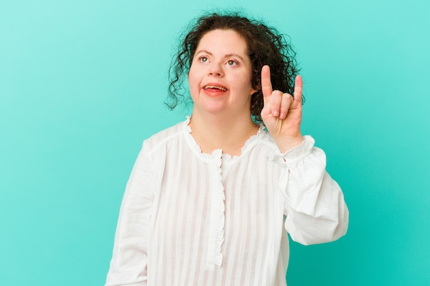 Kobieta z zespołem downa na białym tle pokazując gest rogów