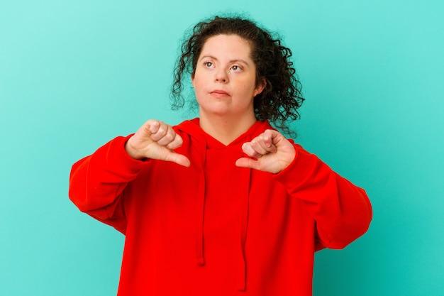 Kobieta z zespołem downa na białym tle pokazująca kciuk w dół i wyrażająca niechęć