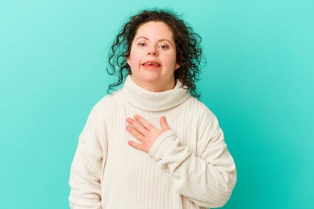 Kobieta z zespołem downa na białym tle śmieje się głośno trzymając rękę na klatce piersiowej