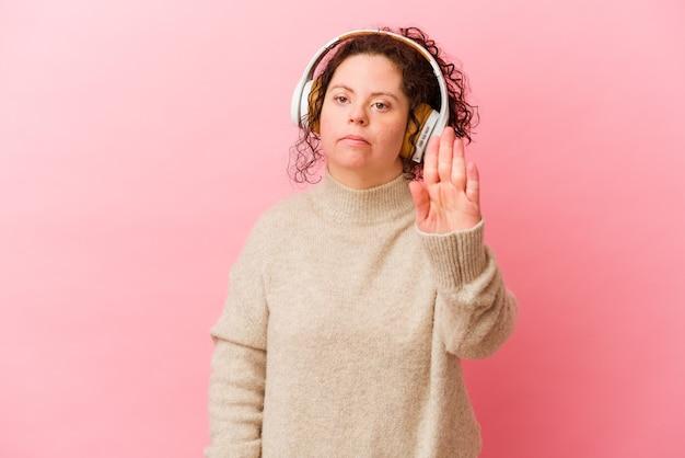 Kobieta z zespołem downa ze słuchawkami na białym tle na różowym tle stojąc z wyciągniętą ręką pokazując znak stopu, uniemożliwiając ci.