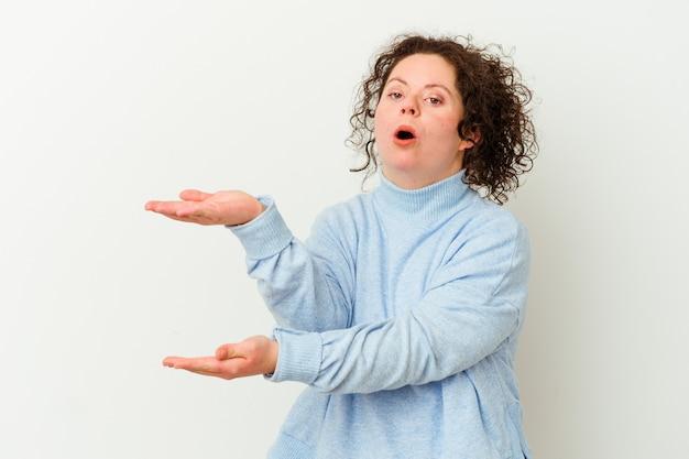 Kobieta z zespołem downa zszokowana i zdumiona trzymająca kopię przestrzeni między rękami.