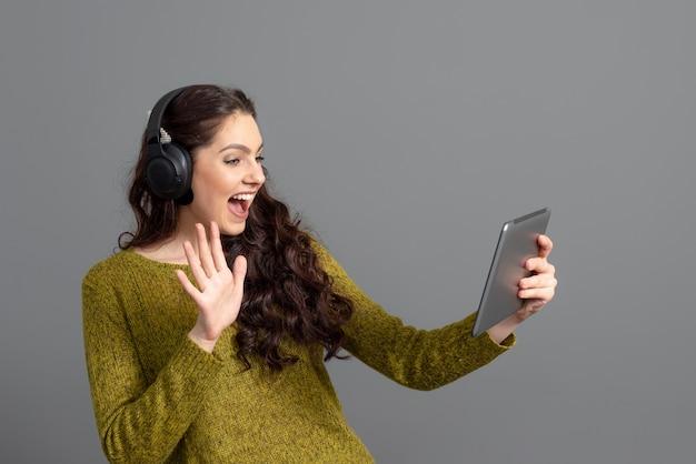 Kobieta z zestawem słuchawkowym i tabletem w ręku, grając w gry i rozmawiając z przyjaciółmi online